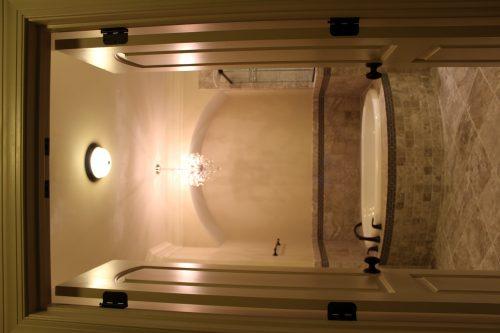 A tile bathroom with a white bathtub