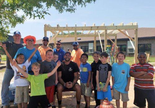 kids and men building a shelter